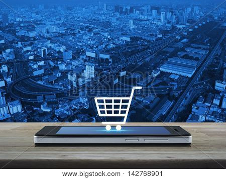 Shopping cart icon on modern smart phone screen on wooden table over city tower street and expressway Shop online concept