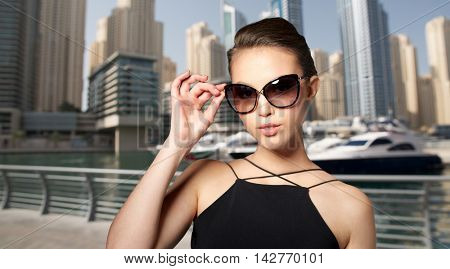 accessories, eyewear, fashion, people and luxury concept - beautiful young woman in elegant black sunglasses over dubai city port background
