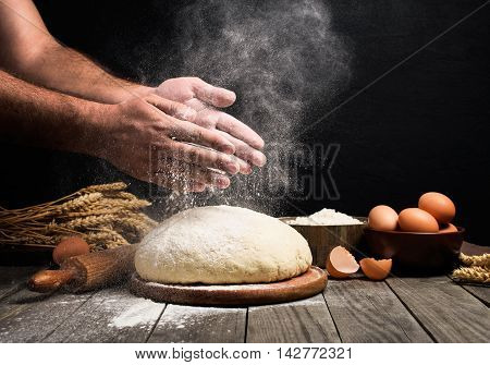 Baker cooking bread. Man slaps flour over the dough. Man Making bread poster