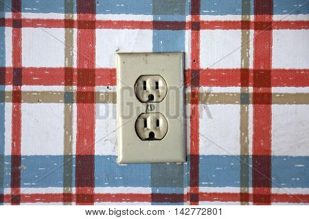 Old dangerous looking wall electrical socket on a plaid wall