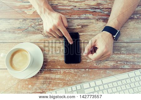 business, technology and people concept - close up of male hand holding smart phone and wearing watch with coffee and keyboard at wooden table