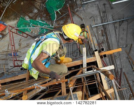 MELAKA, MALAYSIA -JULY 05, 2016: Construction workers wearing safety harness and adequate safety gear while working at high level at the construction site in Melaka, Malaysia.