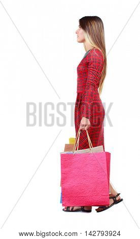 side view of going  woman  with shopping bags . beautiful girl in motion.  backside view of person.  Rear view people collection. Isolated over white background. The girl in red plaid dress goes