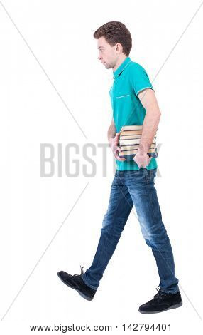 side view of going  man carries a stack of books. walking young guy . Rear view people collection.  backside view of person.  Isolated over white background. Curly kid in a turquoise jacket goes to