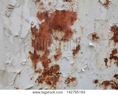 Old paint flaking on the rusty metal hull of a ship
