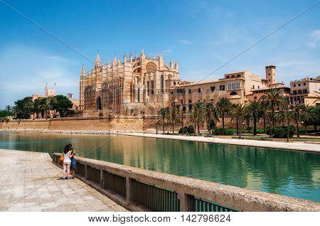Palma de Mallorca Spain - May 27 2016: Park de la Mar against La Seu the gothic medieval cathedral of Palma de Mallorca Spain. The Cathedral of Santa Maria of Palma