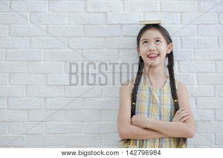 Funny action portrait of Asian girl reading story book on white brick wall