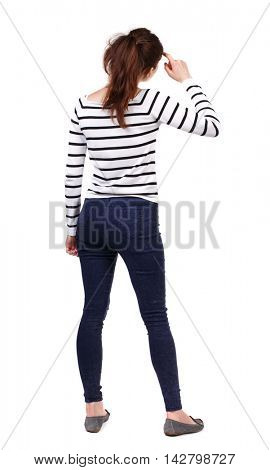 back view of standing young beautiful  woman.  girl  watching. Rear view people collection.  backside view of person.  Girl in a striped sweater thoughtfully scratching his head.