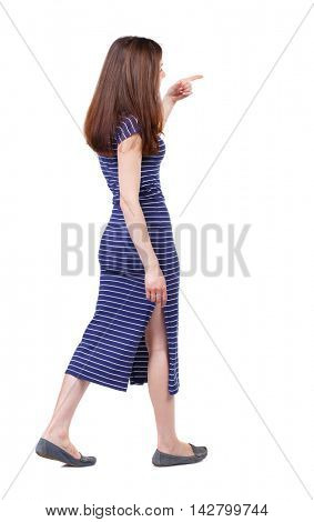 back view of pointing walking  woman. going girl pointing.  backside view of person.  Rear view people collection. Isolated over white background. The brunette in a blue striped dress goes on the side