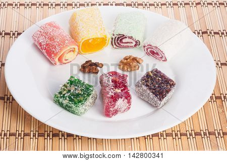 Multicolored round Turkish delight on a white plate