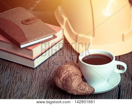 Croissant and cup of coffee on old wood table