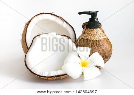 Coconut and coconut oil botton with plumeria or frangipani flower isolated on white background