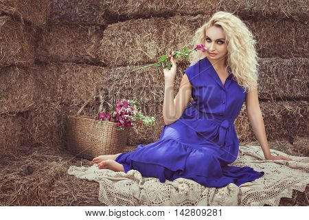 Beautiful blonde woman in the hayloft in the village she flirts holding a flower.