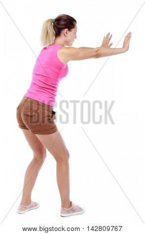 back view of woman pushes wall.  Isolated over white background. Rear view people collection. backside view of person. Sport blond in brown shorts shows stop sign.