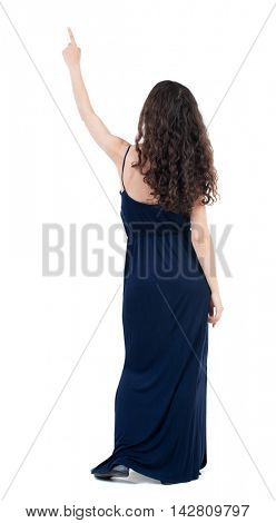 Back view of  pointing woman. beautiful girl. Rear view people collection.  backside view of person.  Isolated over white background. The dark curly girl in a blue evening dress is pointing to the sky