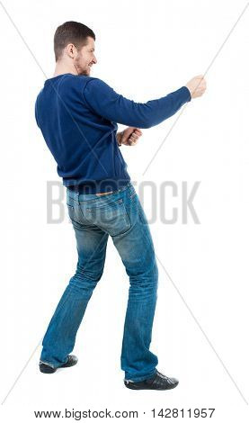 back view of standing man pulling a rope from the top or cling to something.  Rear view people collection.  backside view of person.  Isolated over white background. bearded man in blue pullover pulls