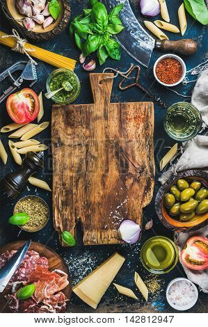 Italian food cooking ingredients on dark background with rustic wooden chopping board in center, top view, copy space, vertical composition