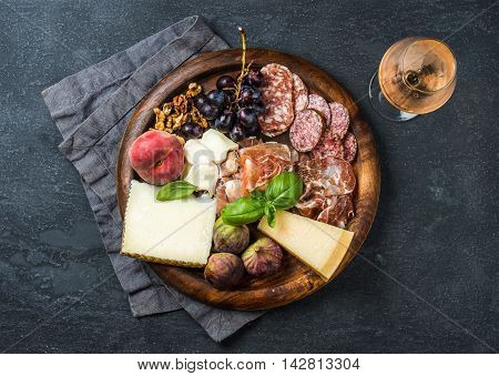 Italian antipasti snack for wine. Prosciutto di Parma, salami, cheese variety, figs, grapes, peach, walnuts and fresh basil on wooden serving tray with glass of Rose, dark grunge background. Top view