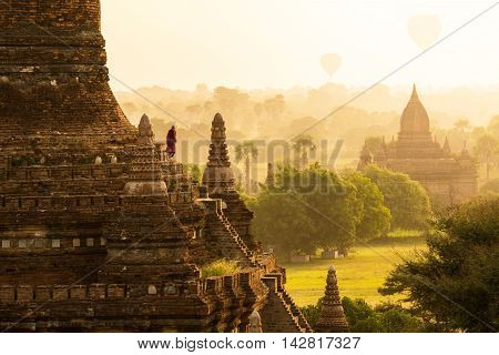 Monk and Hot air ballons over pagodas in sunrise at Bagan Myanmar.