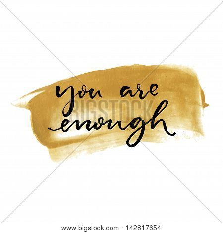 You are enough. Inspirational quote handwritten on golden paint stroke