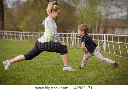 Happy son and mother are doing exercises in the summer park. on the stadium outdoor. Sport activities with children. Healthy lifestyle. Fitness exercises. Young mother and son are stretching together poster