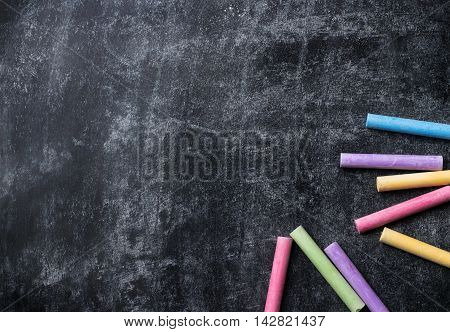 Education, back to school concept. Pieces of school chalk on old black chalkboard. Selective focus, top view, flat lay, copy space background