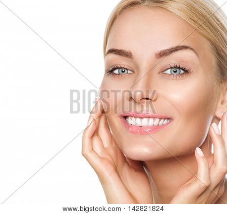 Beauty model woman touching her face. Beautiful Spa model Girl with Perfect Fresh Clean Skin. Blonde female looking at camera and smiling. Youth and Skin Care Concept. Isolated on a white background