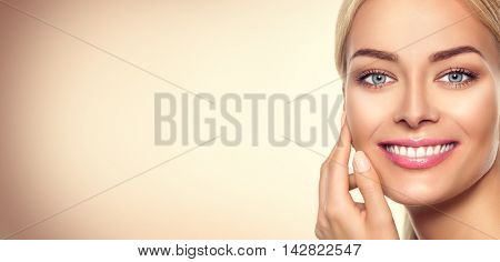 Beauty model woman face. Beauty Girl Portrait. Beautiful Lady Girl Touching her Face and smiling. Perfect Fresh Skin. Pure Beauty Model Female looking at camera. Youth and Skin Care Concept