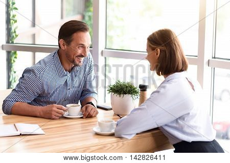 Pleasant talk. Joyful smiling colleagues sitting at the table and talking while drinking coffee