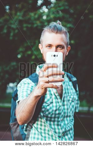 Selfie Photo concept. Young bearded man holding camera phone and taking photo with white smartphone. Selective focus on mobile. Close up lifestyle portrait of young male with evening warm sunlight background.