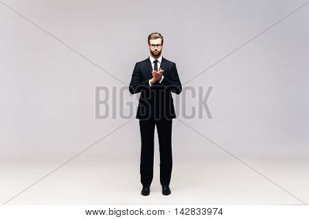 Confident businessman. Full length studio shot of handsome young man in full suit keeping hands clasped and looking at camera