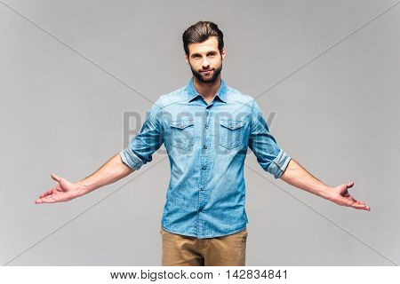 Always true. Studio shot of handsome young man in casual wear looking at camera and keeping hands outstretched