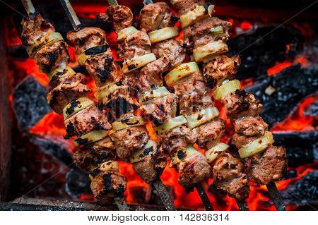 Barbecue Pork Kebabs On The Hot Grill Close-up. Flames Of Fire And Coals In The Background
