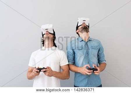 poster of Time for hobby. Cheerful involved men holding heads up and playing video games while using virtual reality glasses