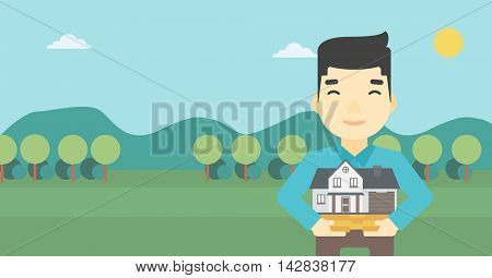An asian young man holding house model in hands on the background of mountains. Real estate agent with house model. Vector flat design illustration. Horizontal layout.