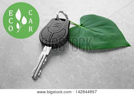 Car key with green leaf trinket and text ecocar on gray background. Eco transport concept.