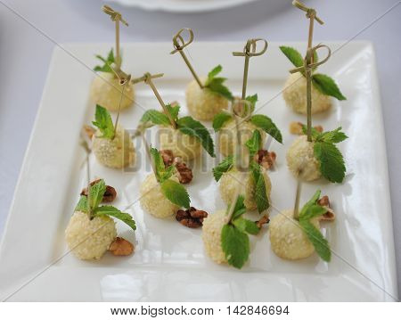 Canapes with bocconcini with sesame and mint on white plate