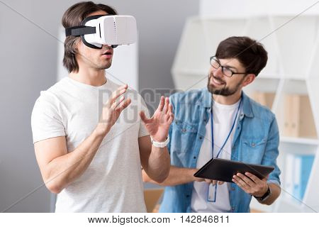 Check it out. Cheerful colleagues using virtual reality device while testing it and working together