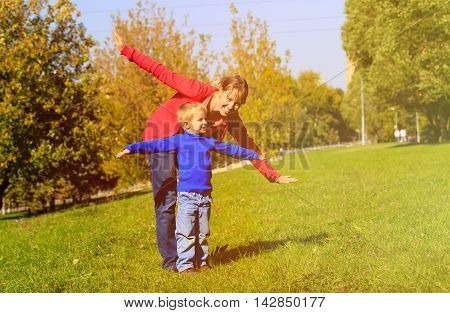 mother and son play in autumn nature, family fun