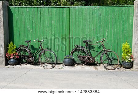 Two decorative bicycles on the street near green gate