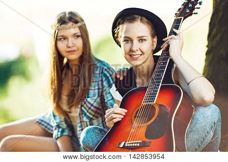 Two beautiful young women playing guitar on a picnic; selective focus