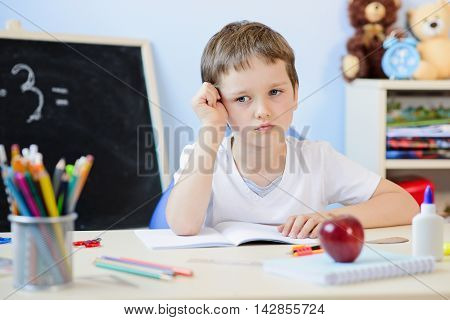 7 years old boy doing his homework and wonders about the solution. Back to school