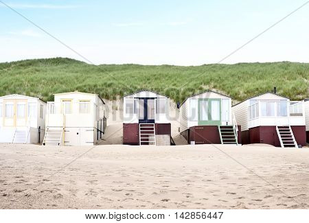 beach huts or houses and clear sky. Beach huts in front of a beach dune.