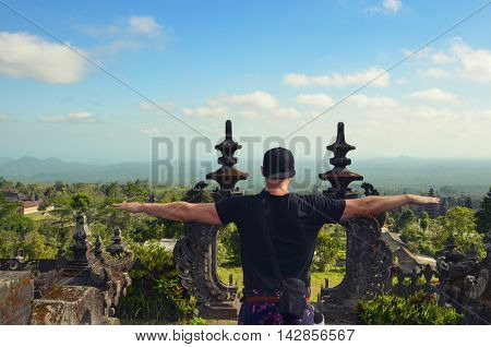Young backpacker tourist on Bali visits a Hindu temple on a volcano mountain - mother temple Besakih