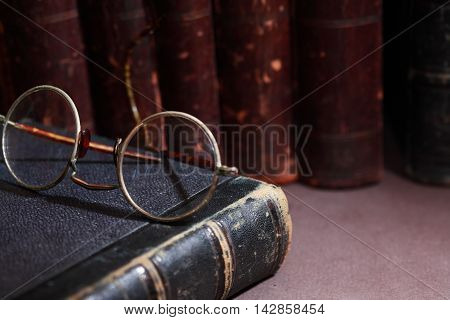 Vintage library. Old spectacles against old book in a row on dark background