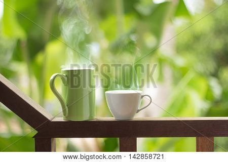 Hot Drink Cups With Smoke On Wooden Balusters In Balcony