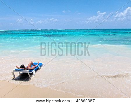 Woman on blue recliner on a white sand beach