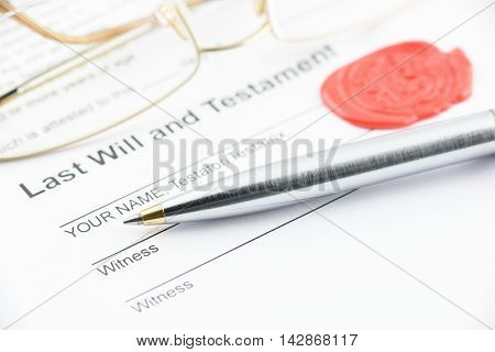 Blue ballpoint pen on last will and testament with eye glasses and a sealing wax stamped with alphabet letter B. Preparation for filling and signing a document.