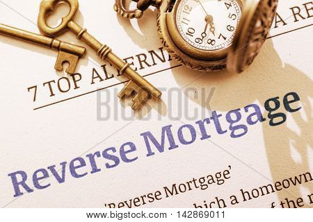 Vintage / retro color style with a long shadow : Two brass keys and a pocket watch on a reverse mortgage instruction document. A concept for a mortgage which an elder who want to turn assets into cash.