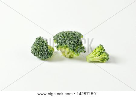 Fresh broccoli florets on off-white background